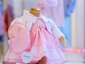 Image of a pink baby's dress and white cardigan